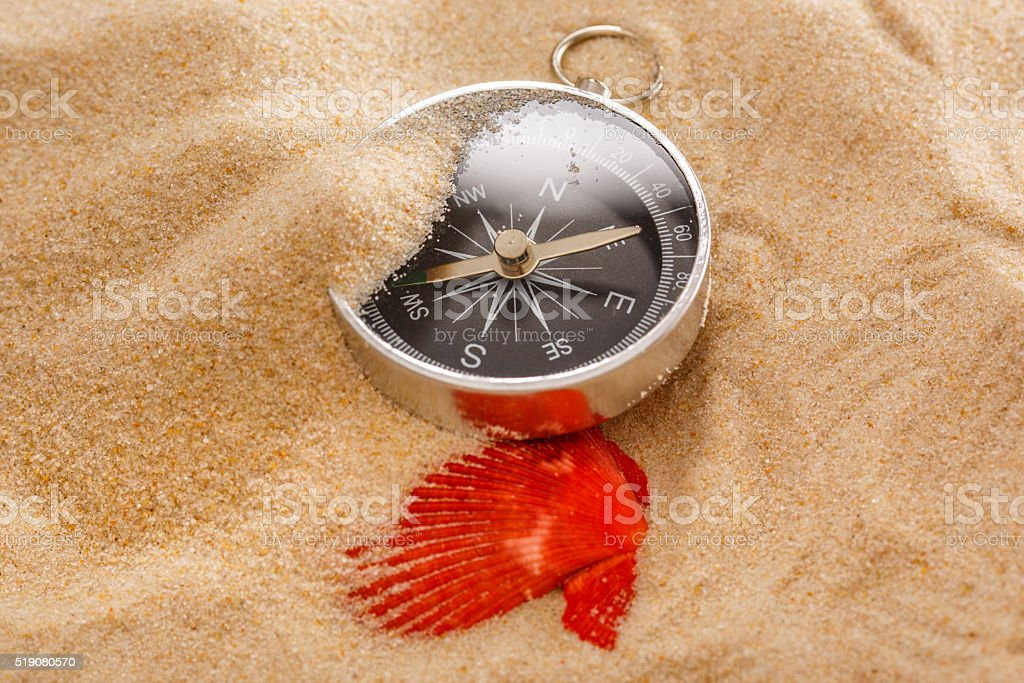 Black compass and sea shell in sand stock photo