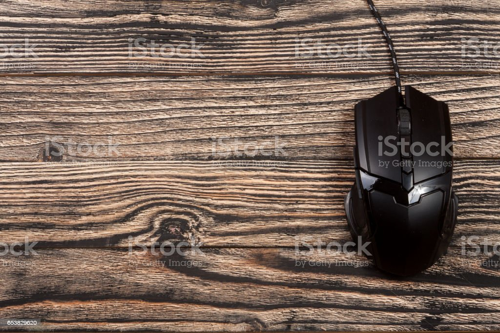 black computer mouse on a black wooden background with copy space for your text. Top view stock photo