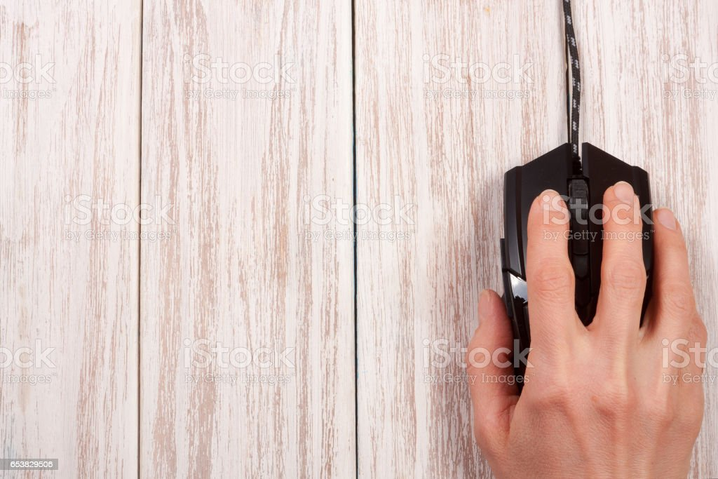 black computer mouse with a hand on a white wooden background with copy space for your text. Top view stock photo