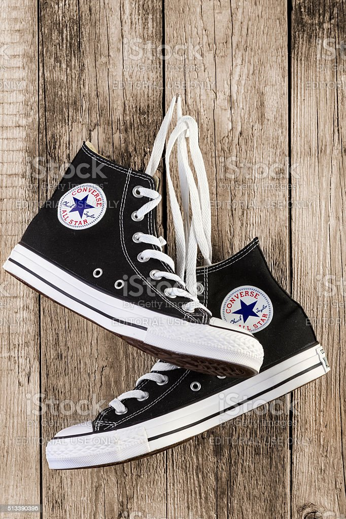 Black Converse shoes on wooden stock photo