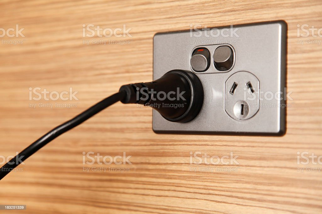 A black cord plugged into a power point on a wooden wall royalty-free stock photo