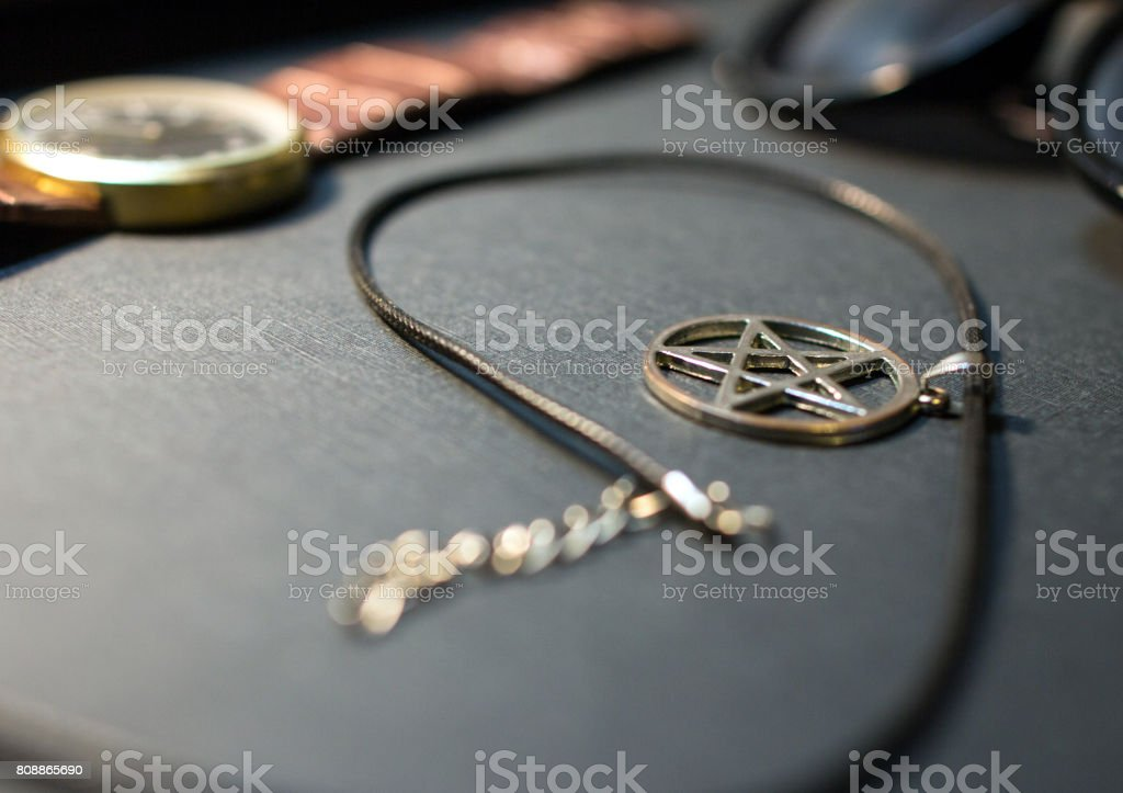 Black cord silver pentagram pendant necklace with leather strap watch and sunglasses stock photo