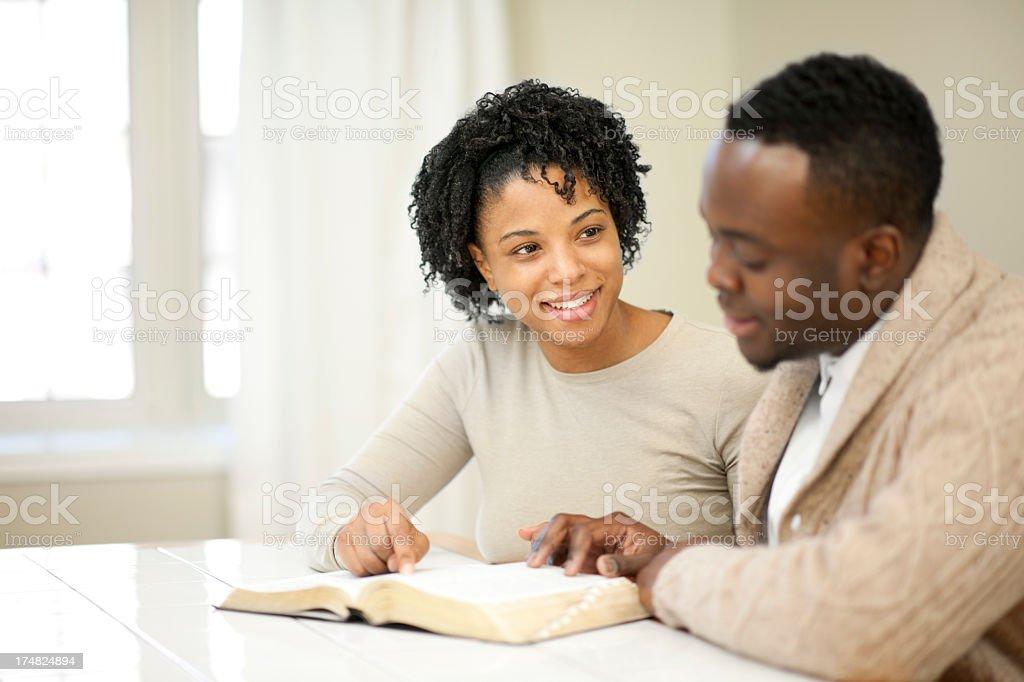 black couple reading bible stock photo