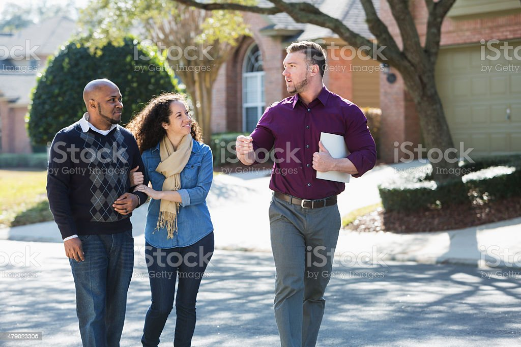 Black couple walking on residential street with agent stock photo