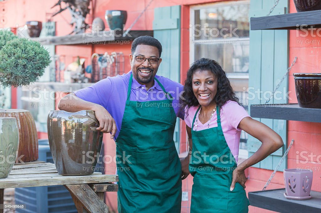 Black couple working in plant nursery stock photo