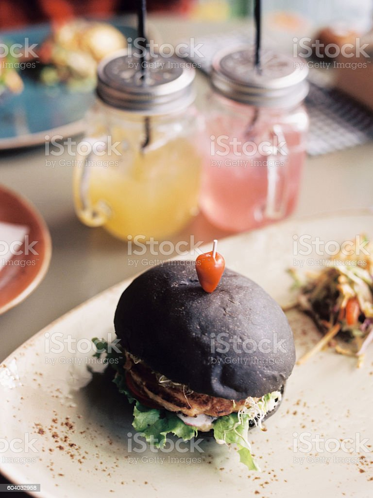 Black craft burger with bacon and rustic drinks royalty-free stock photo