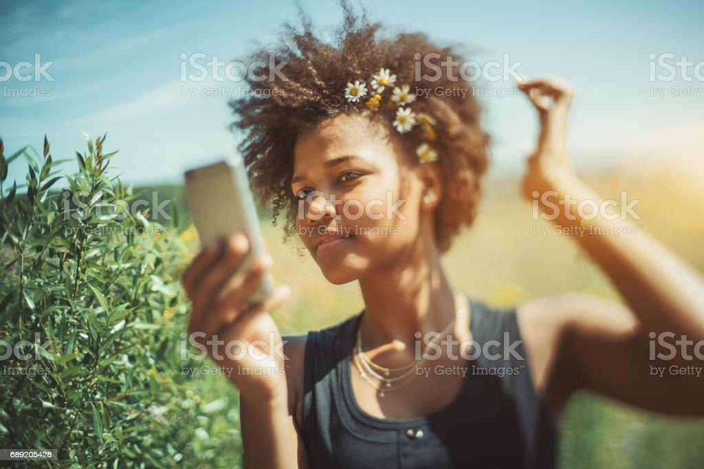 Black curly teenage female is making selfie stock photo