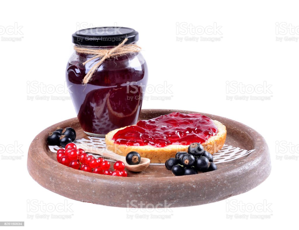 Black currant jam on a slice and in a jar, stock photo