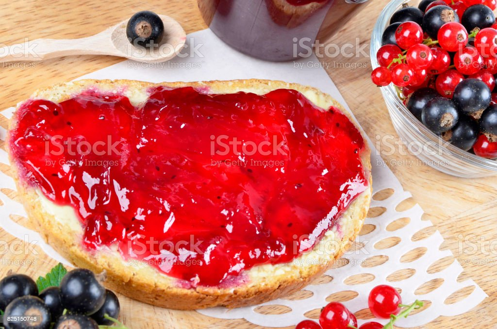 Black currant jam on a slice and in a jar stock photo
