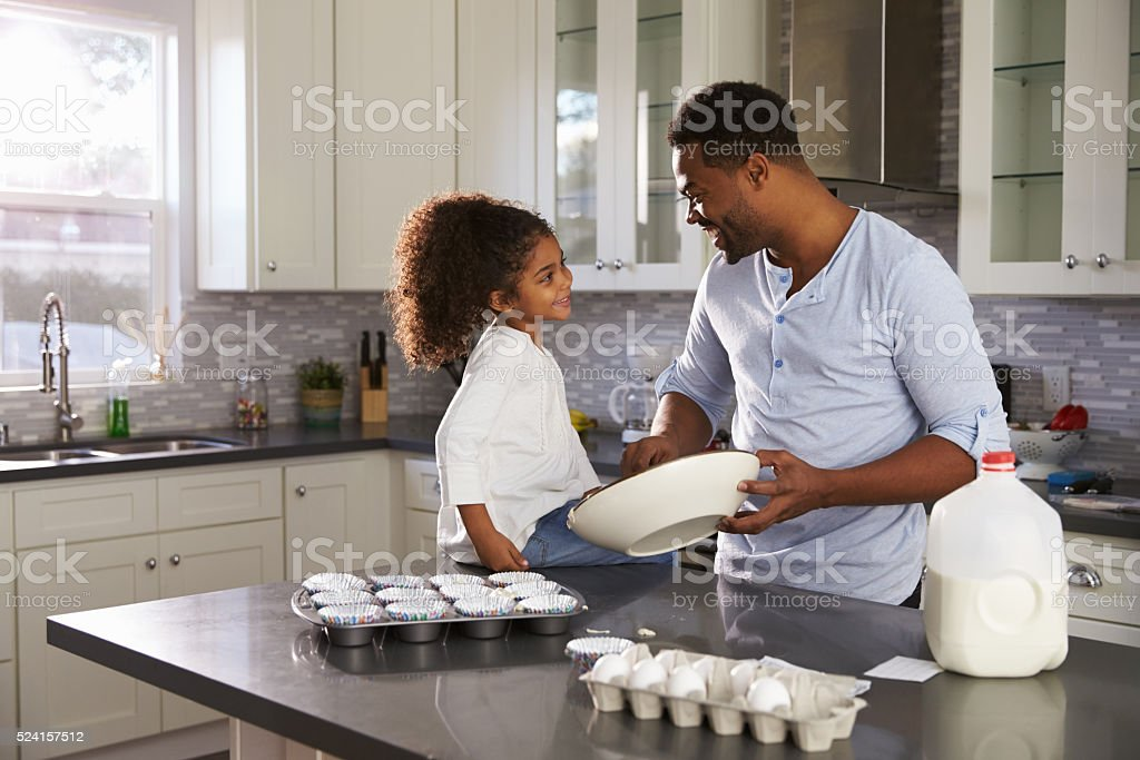 Black dad and young daughter look at each other while stock photo