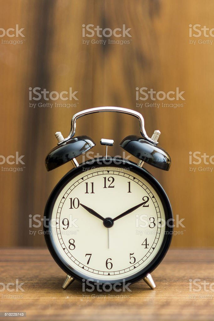 Black desk clock standing on the wooden table stock photo