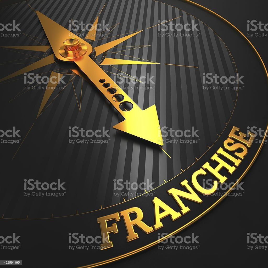 Black dial with gold arrow pointing at franchise stock photo