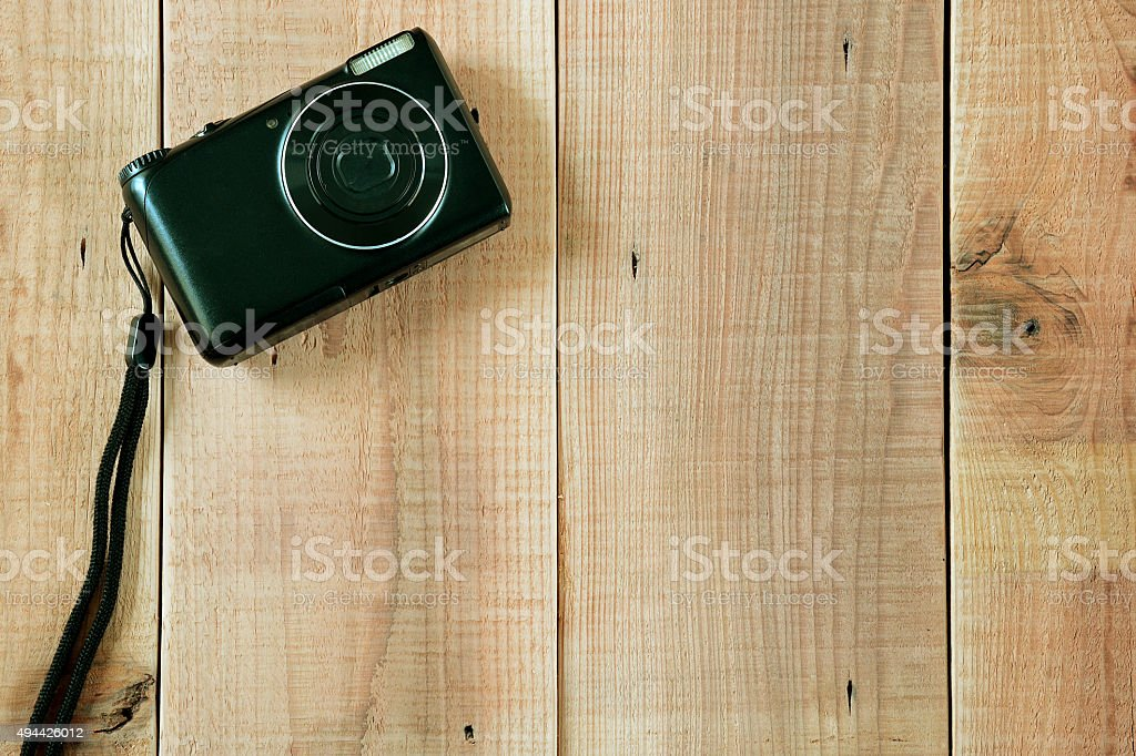 Black digital camera on wooden background. stock photo