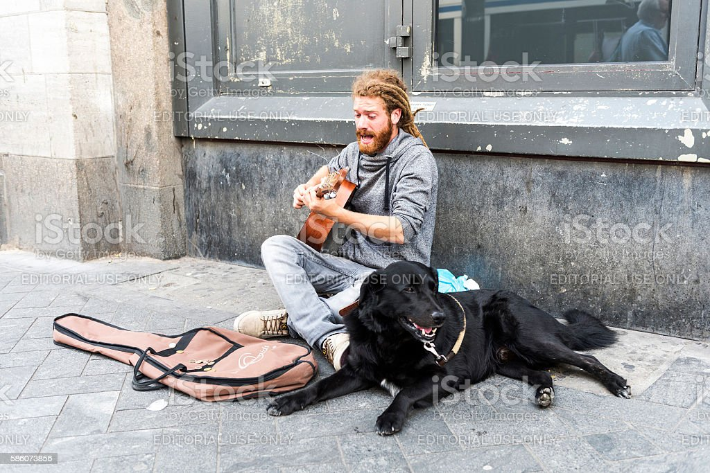 Black dog and street musician is playing guitar in Amsterdam stock photo