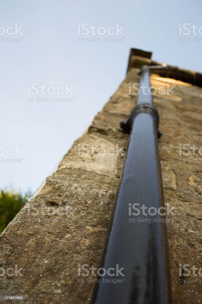 Black Drainpipe on a Cottage Wall royalty-free stock photo