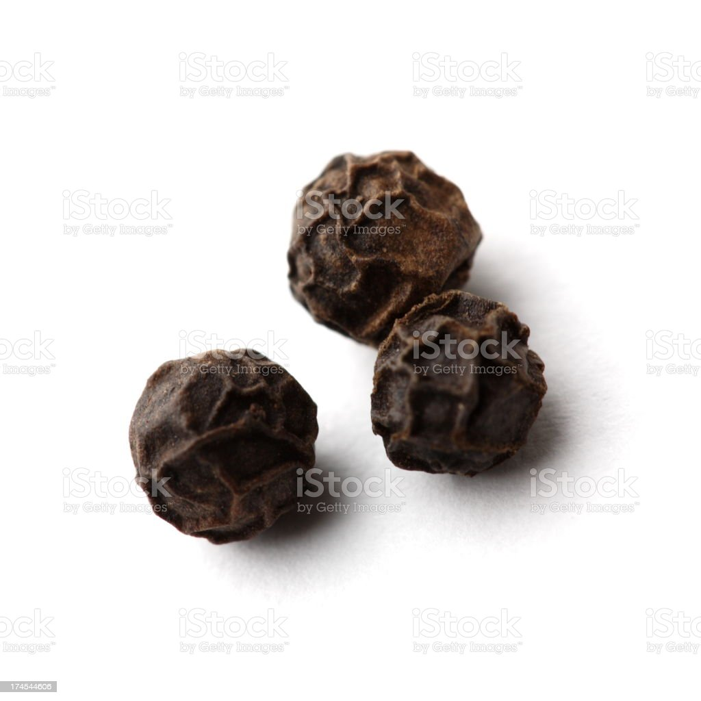 Black dried out peppers on white background stock photo