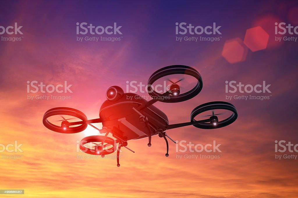 Black drone flying in the sky at sunset, lens flare stock photo