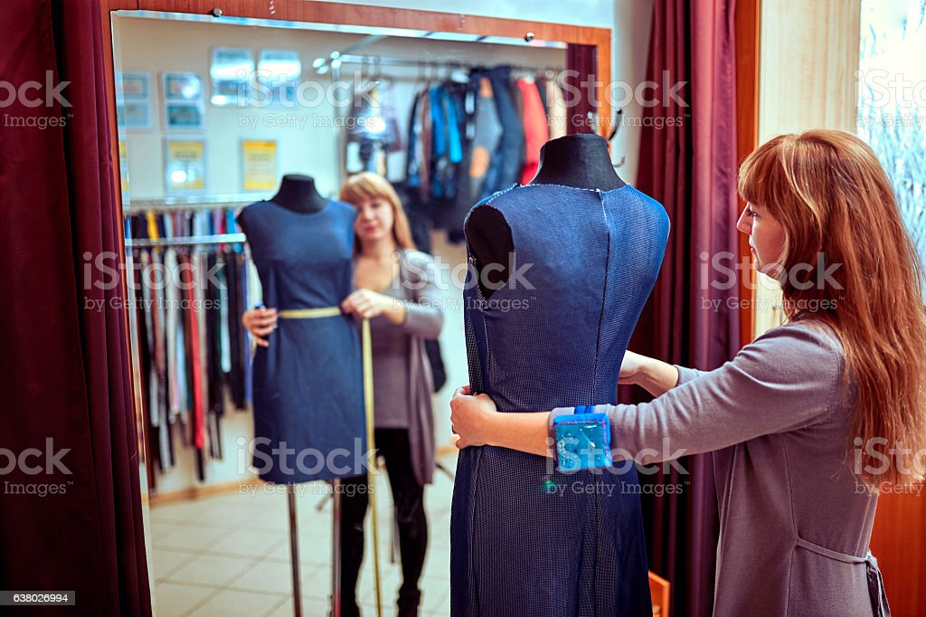 Black dummy with measuring tape in tailors studio stock photo