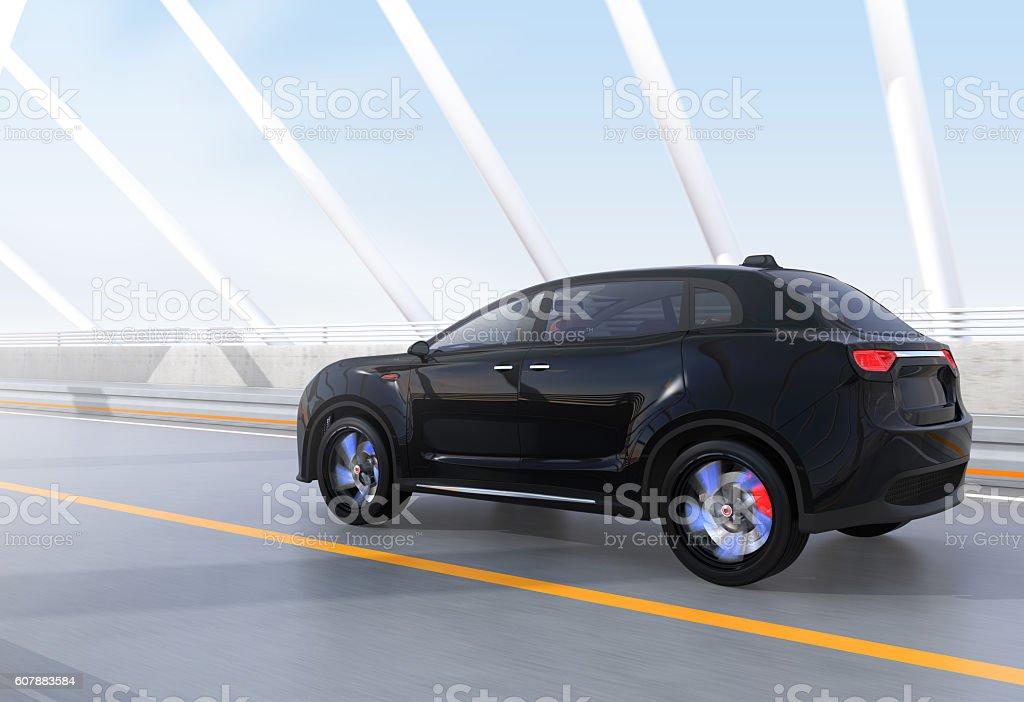 Black electric SUV driving on arc bridge stock photo