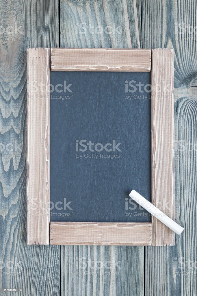 Black empty chalkboard on wooden table for copy space, vertical, top view stock photo