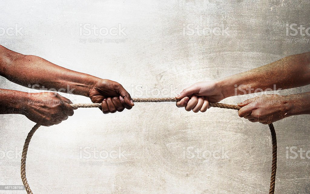 black ethnicity hands pulling rope against white Caucasian race person stock photo