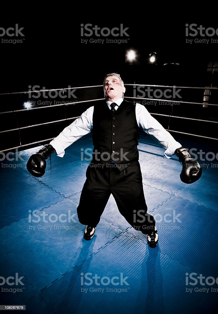 Black Eyed Businessman About to Fall Down in Boxing Ring royalty-free stock photo