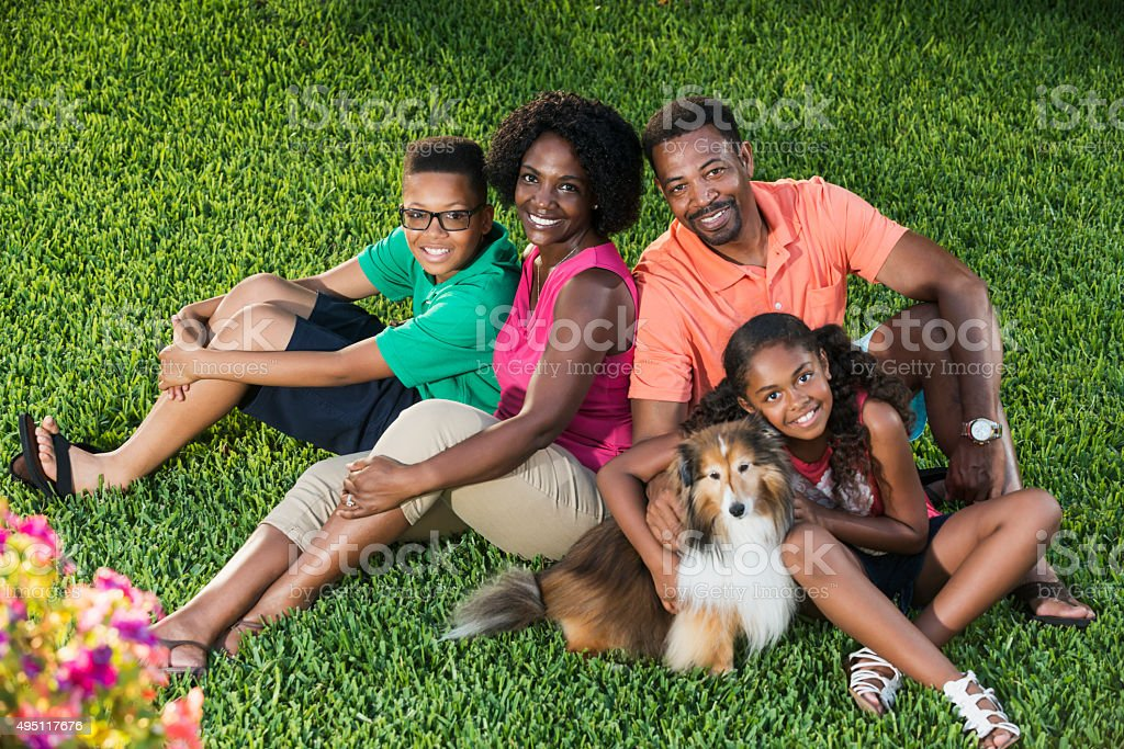 Black family of four sitting together on grass with dog stock photo