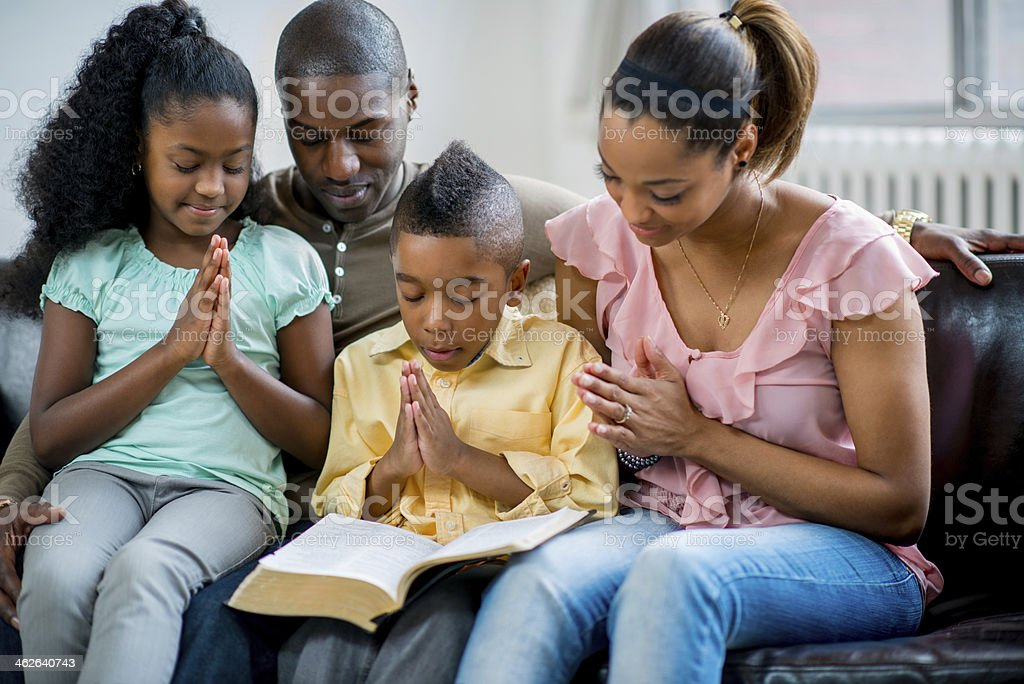 black family praying together stock photo