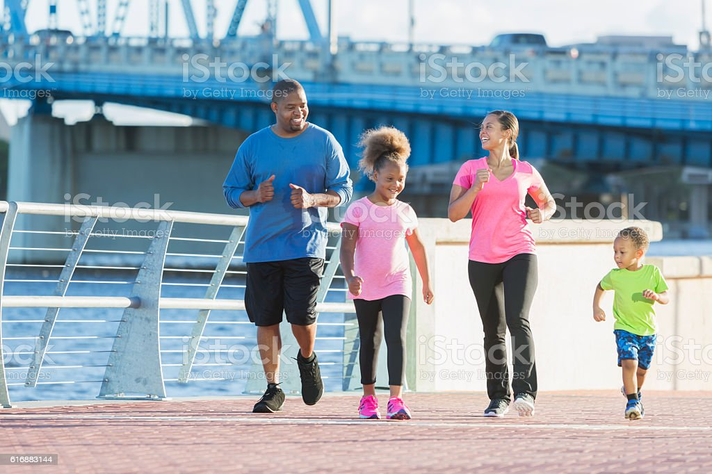 Black family staying fit, power walking on waterfront stock photo