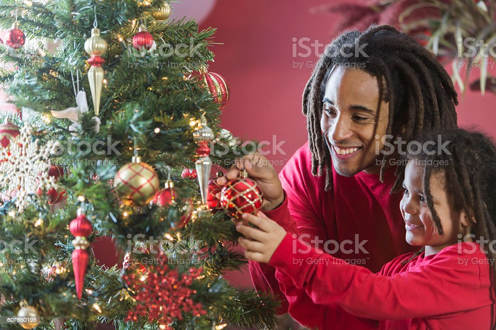 Black father and son decorating Christmas tree stock photo