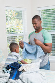 Black father and son folding laundry on bed