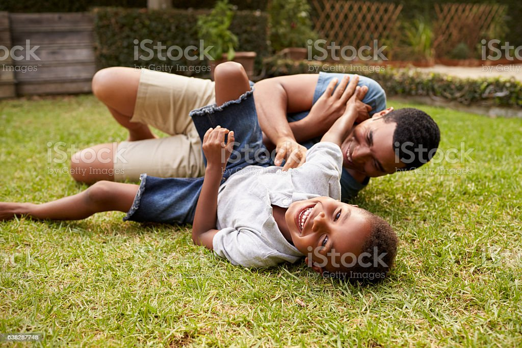 Black father and young son play lying on grass, low stock photo
