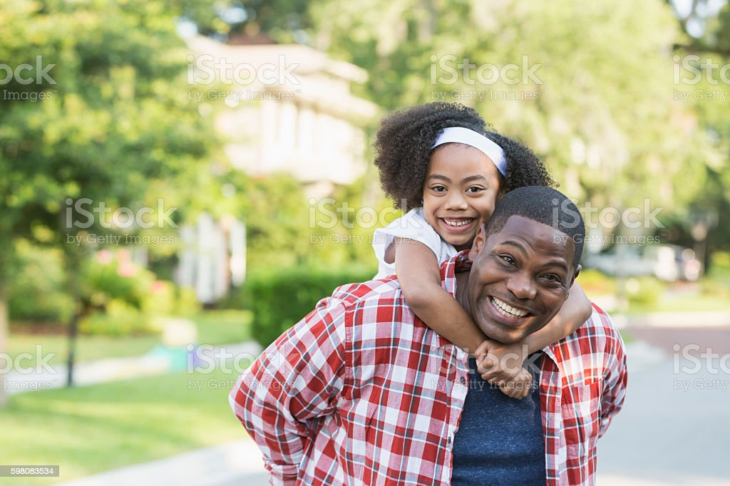 Black father with mixed race daughter, playing piggyback stock photo