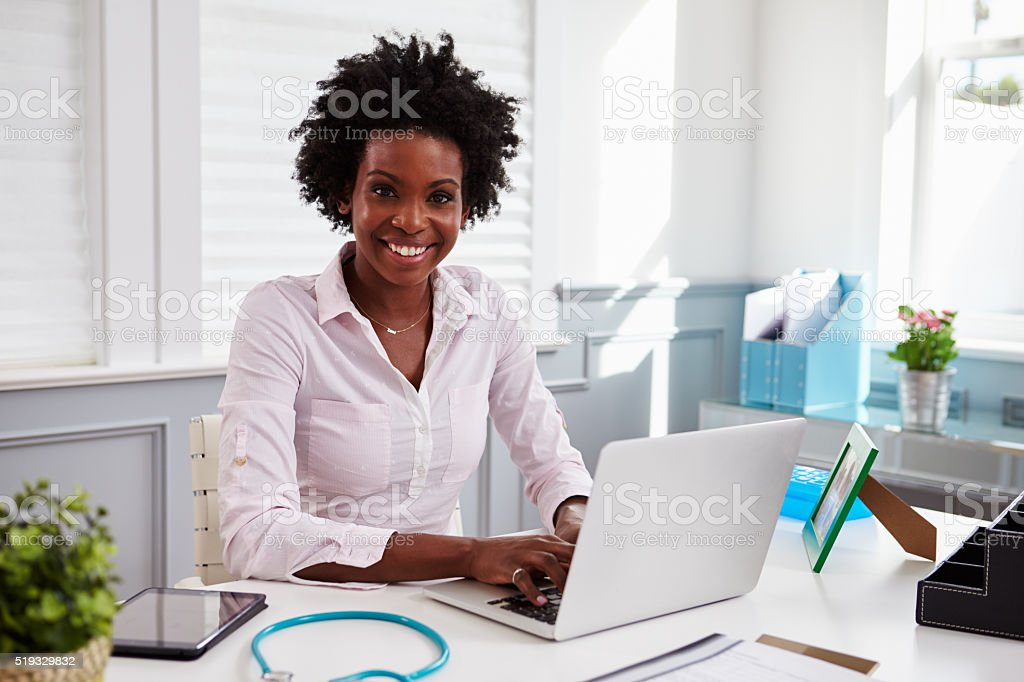 Black female doctor at work in an office, looking stock photo