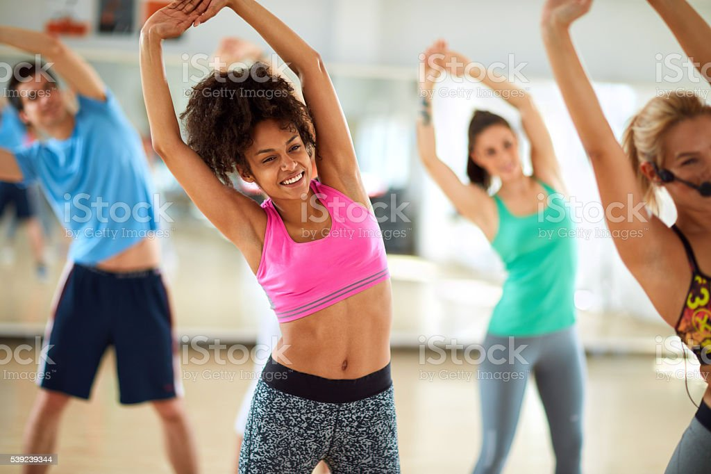 Black female doing stretching exercises in group stock photo