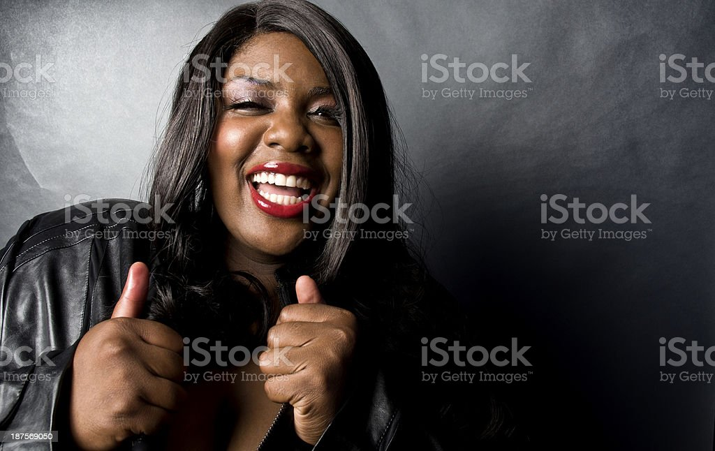 Black Female Model Happy Pose In Leather Jacket Thumbs Up royalty-free stock photo