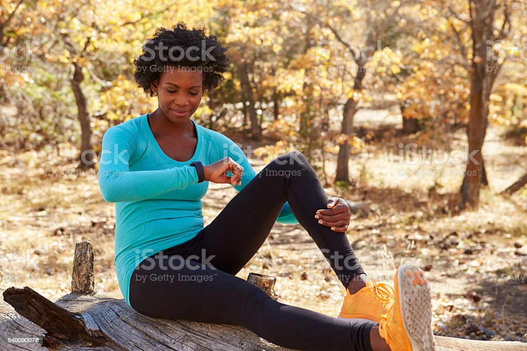 Black female runner sitting in a forest checking smartwatch stock photo