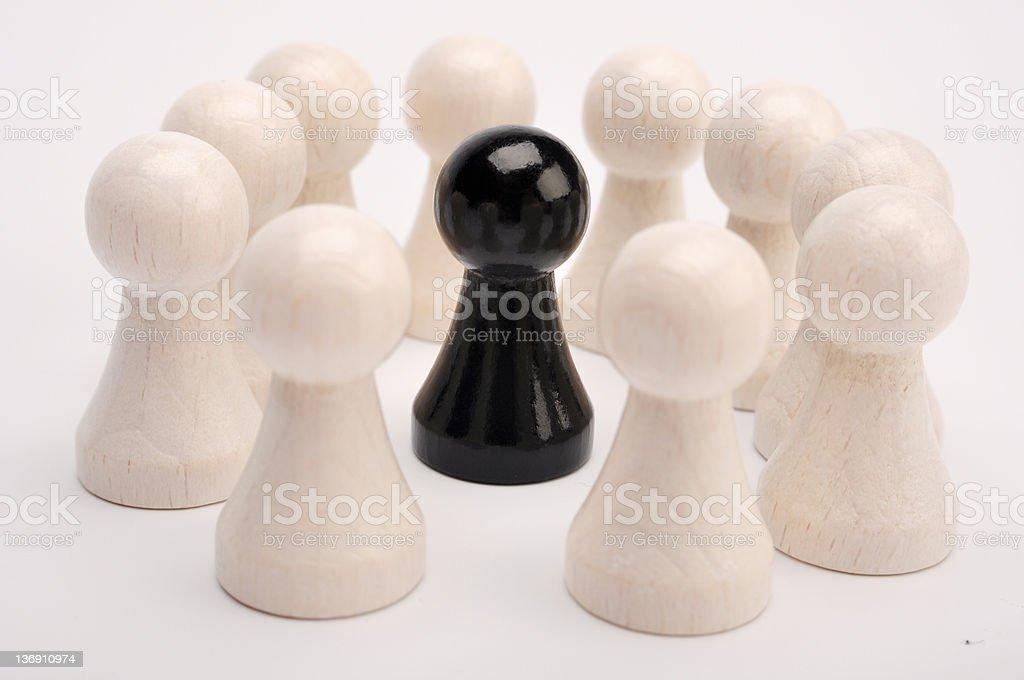 Noir figurine entourée de figurines blanc photo libre de droits