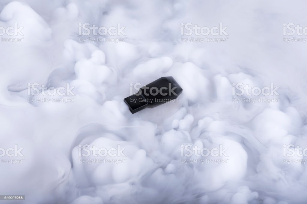 Black flash memory stick in the Information clouds stock photo