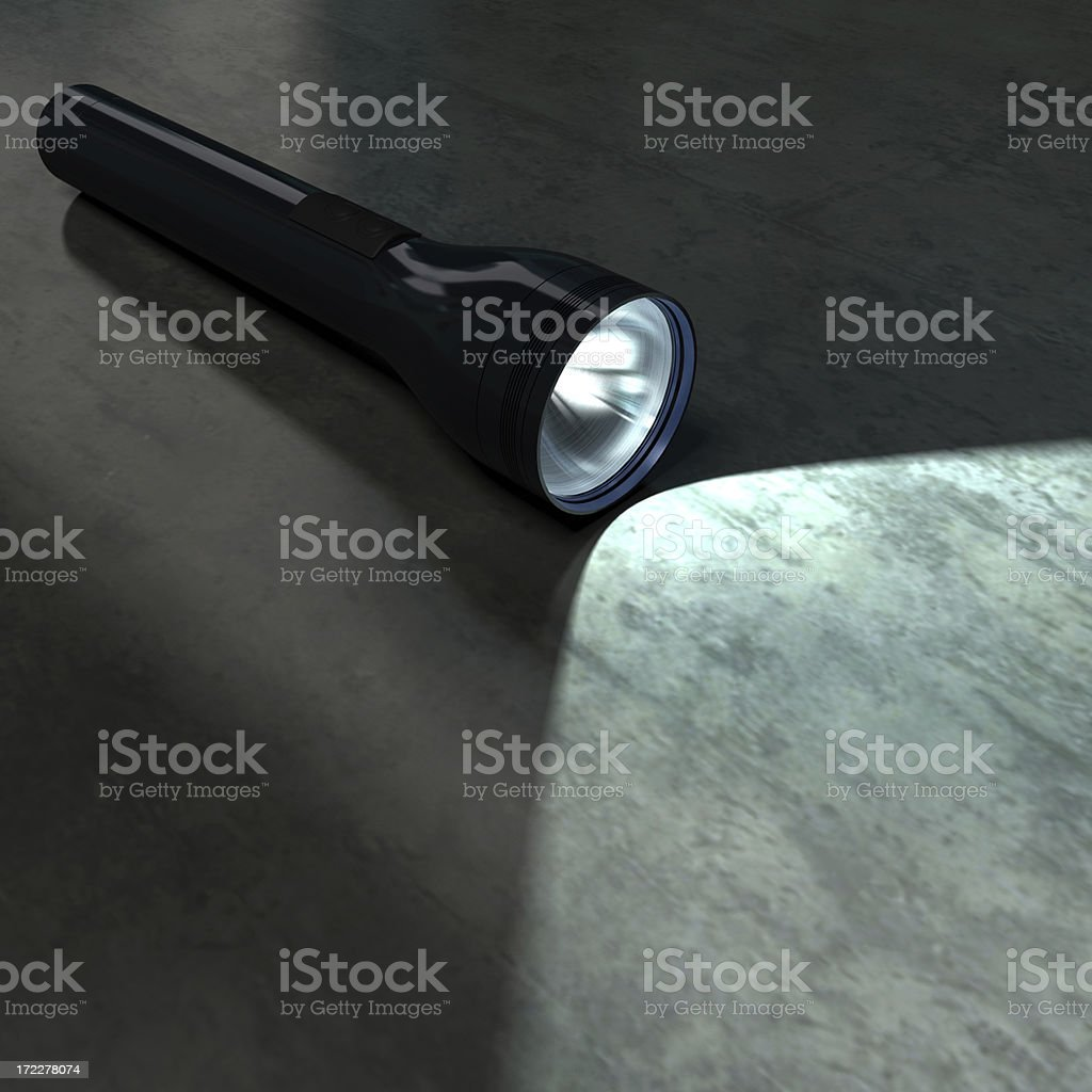 Black flashlight illuminating part of a dark metallic floor stock photo