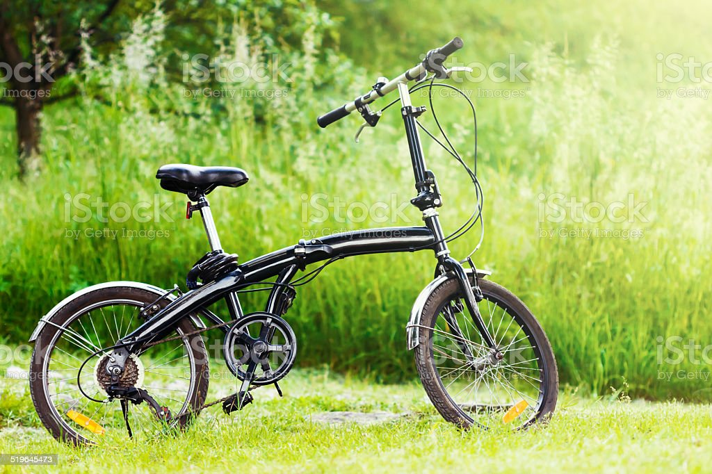 Black folding bicycle in grass stock photo