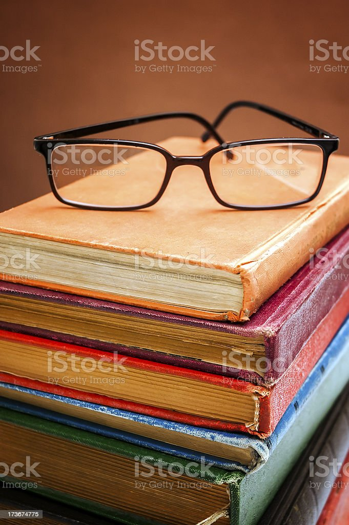 Black framed eye glasses stands on the old books royalty-free stock photo