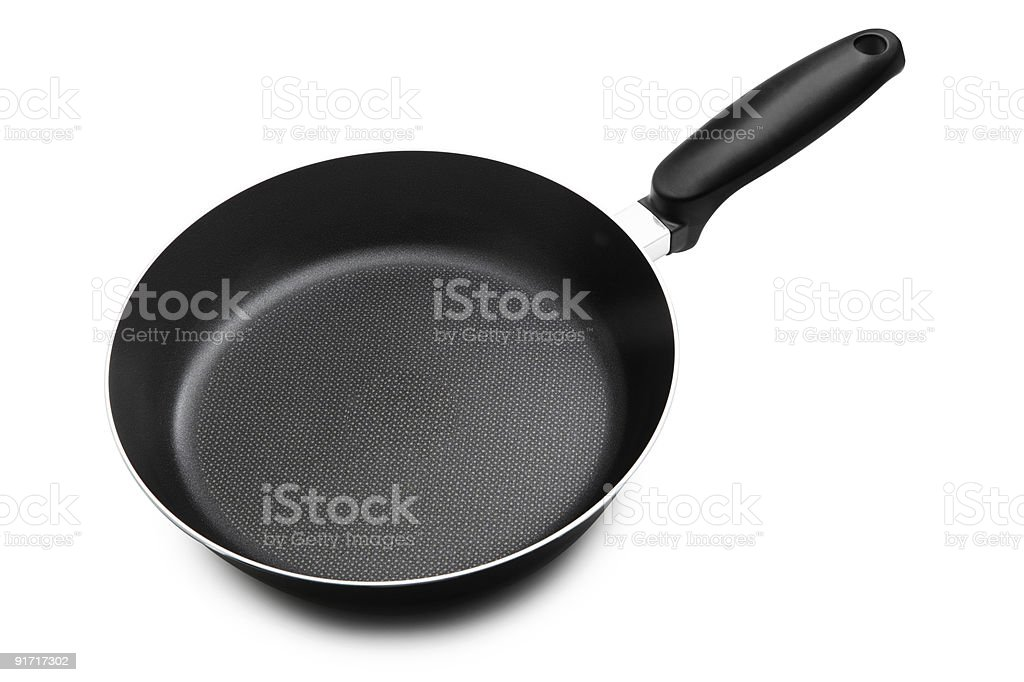 A black frying pan set against a white background stock photo