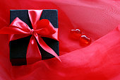 Black gift box with red ribbon on scarlet transparent fabric