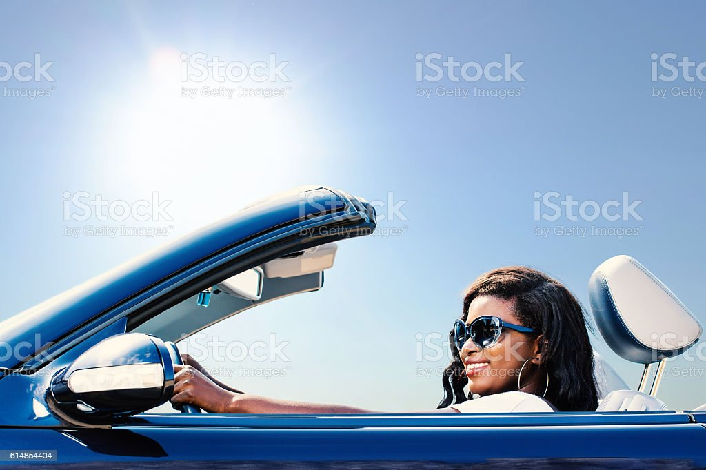 Black girl enjoying drive with convertible. stock photo