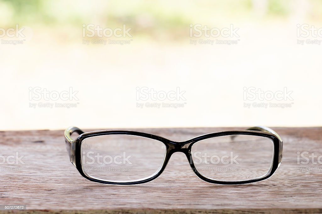 black glasses on old  wood table stock photo