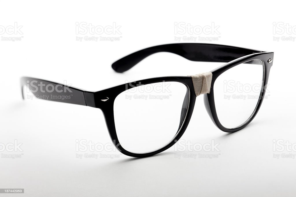 Black glasses with tape on the nosepiece stock photo