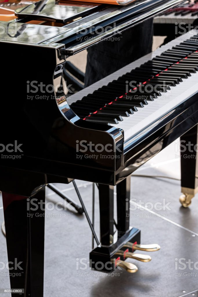 black grand piano with black and white keys on stage stock photo