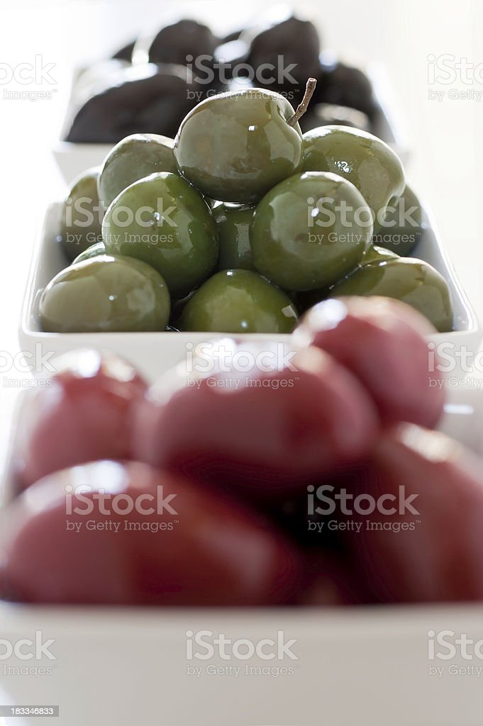 Black, Green, and Red Olive Trio Vertical stock photo