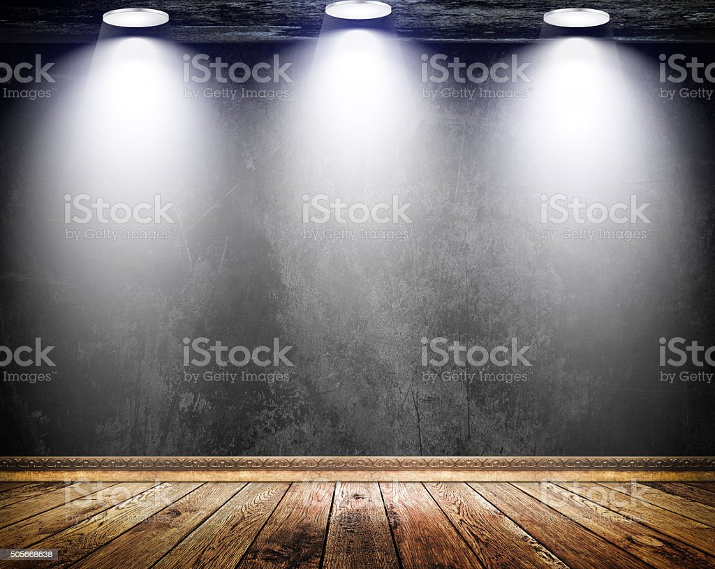 Black grunge wall with three lamps and old wooden floor. stock photo